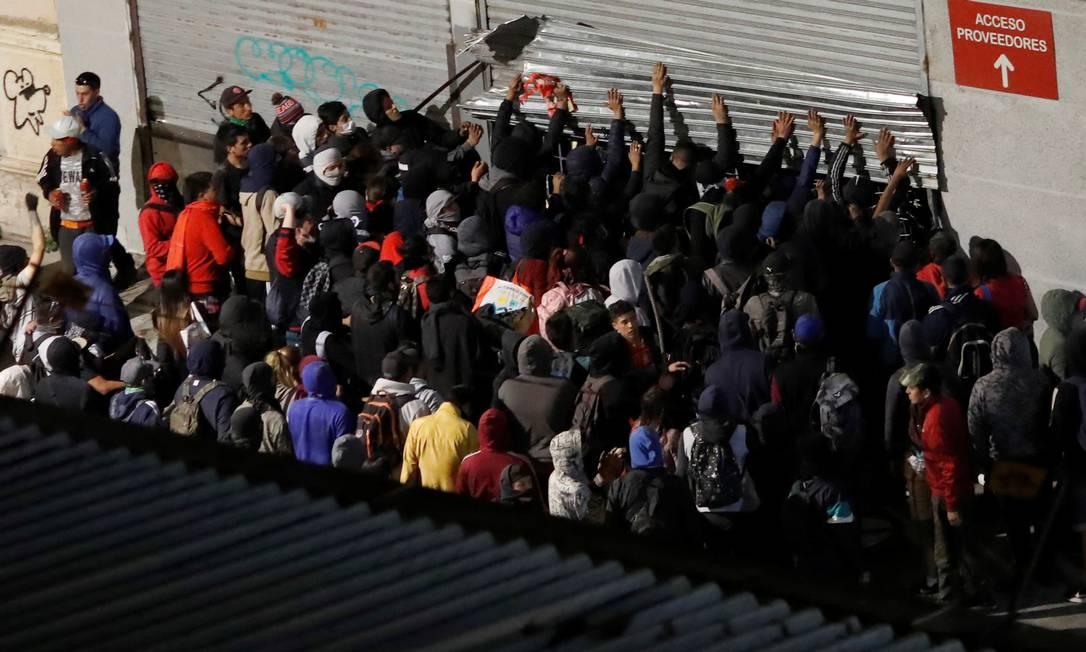 Manifestantes tentam invadir uma loja em Valparaíso; prefeito da cidade disse que foi o pior dia desde o início dos protestos, em 18 de outubro Foto: GORAN TOMASEVIC / REUTERS/26-11/2019