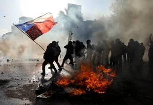 Manifestantes com a bandeira do Chile perto de barricada em chamas em Santiago Foto: PABLO SANHUEZA / REUTERS