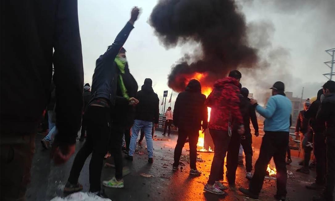 Manifestantes iranianos se reúnem em torno de um incêndio durante uma manifestação contra o aumento dos preços da gasolina na capital Teerã, em 16 de novembro de 2019 Foto: - / AFP