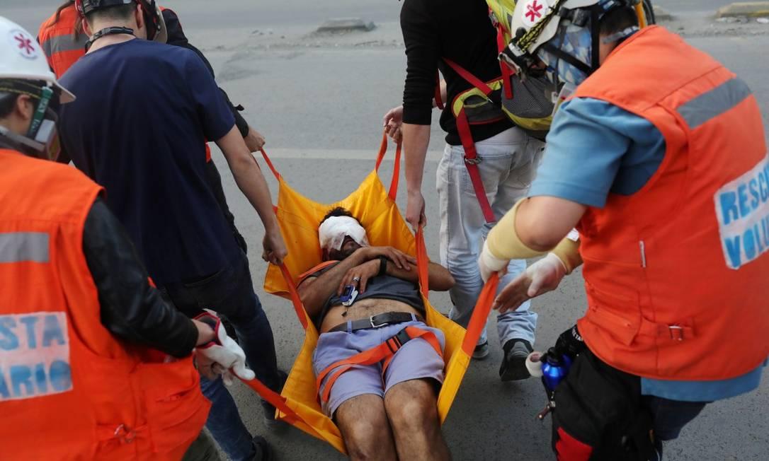 Um manifestante atingido no rosto pela polícia chilena recebe assistência médica em Santiago Foto: PABLO SANHUEZA / REUTERS