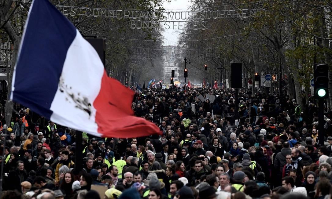Manifestantes balançam bandeira gigante da França em protesto contra reforma da Previdência planejada pelo governo de Emmanuel Macron Foto: PHILIPPE LOPEZ / AFP
