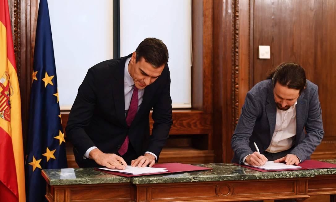 Os líderes do Psoe, Pedro Sánchez, e o do Podemos, Pablo Iglesias, assinam o programa da coalizão de governo Foto: GABRIEL BOUYS / AFP
