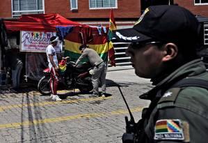 Policial e opositores do ex-presidente boliviano Evo Morales, exilado na Argentina, acampados no condomínio La Rinconada, onde fica a embaixada do México em La Paz Foto: JORGE BERNAL / AFP/30-12-2019