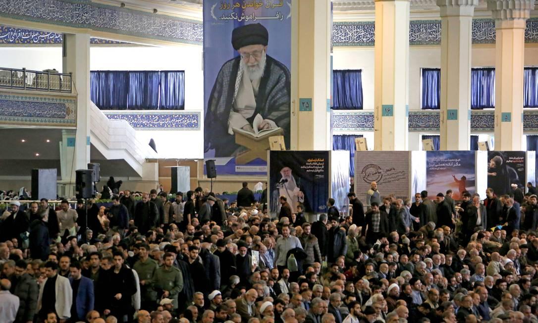 Sob um retrato de Khamenei, iranianos rezam pelo general Qassem Soleimani, morto em ataque americano em Bagdá Foto: ATTA KENARE / AFP