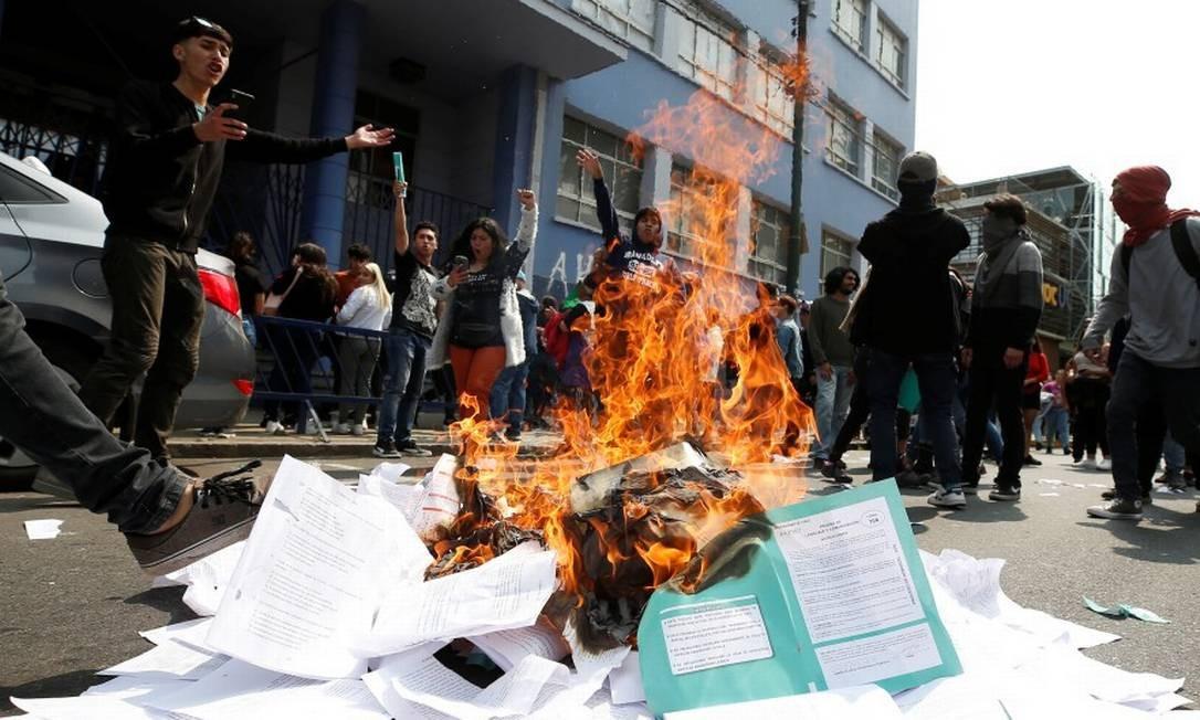 Manifestantes queimam provas em protesto no Chile Foto: RODRIGO GARRIDO / REUTERS