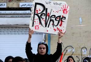 Um cartaz pede revanche, em inglês, no enterro de Soleimani em sua cidade natal, Kerman Foto: ATTA KENARE / AFP/7-1-2020