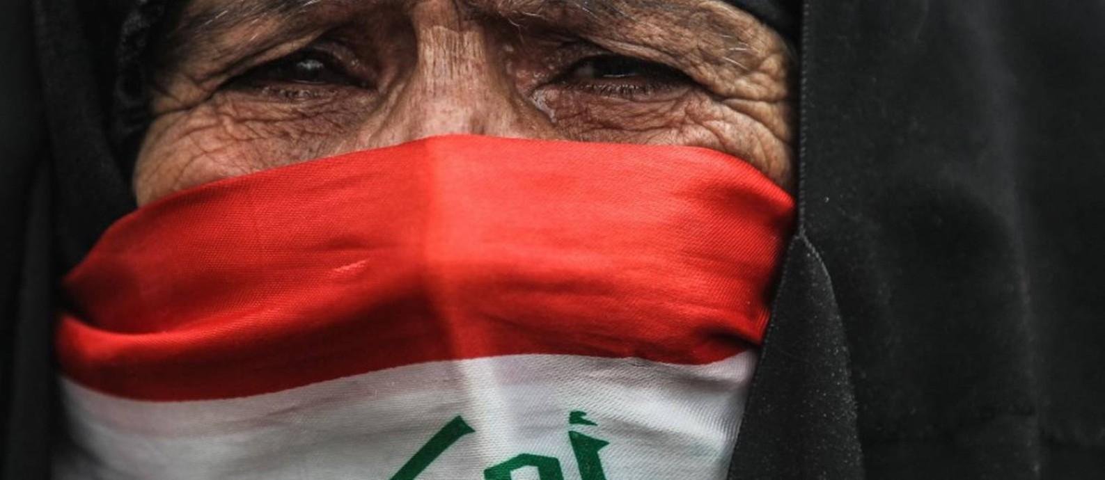 Com o rosto coberto pela bandeira iraquiana, mulher chora durante protesto em Bagdá; oito especialistas falaram ao GLOBO sobre impacto da crise Foto: AHMAD AL-RUBAYE/AFP/10-1-2020