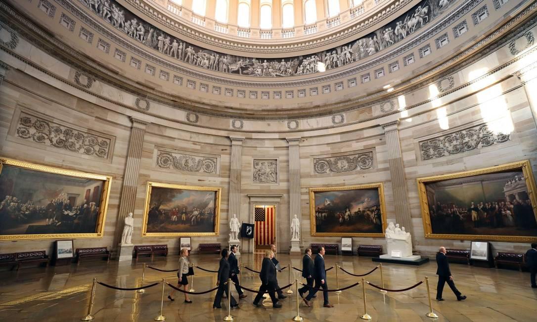 Guaidos pelo sargento de armas Paul Irving, os sete deputados democratas caminham na rotunda do Capitólio, rumo ao Senado dos EUA Foto: CHIP SOMODEVILLA / AFP