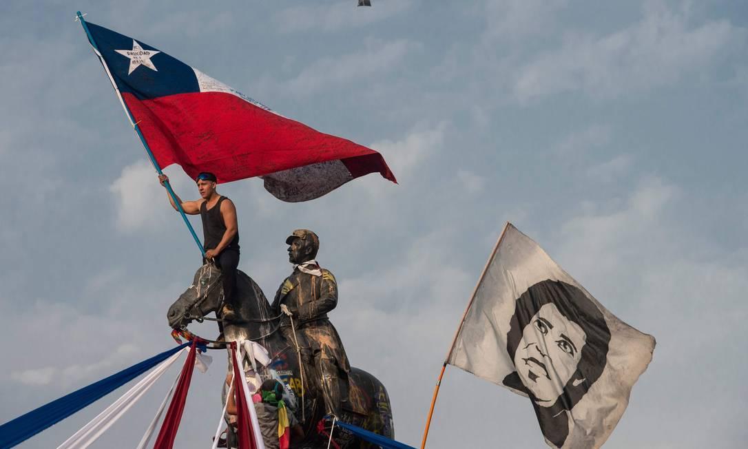 Manifestante em cima da estátua do general Manuel Baquedano (1823-1897), na Praça Itália, em Santiago, epicentro dos protestos Foto: MARTIN BERNETTI / AFP/17-1-2020