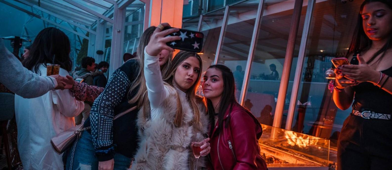 Adolescentes tiram uma selfie em uma festa de aniversário de 17 anos em um bar de Caracas Foto: ADRIANA LOUREIRO FERNANDEZ / NYT 20-12-19