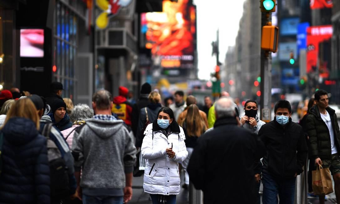Pessoas caminham com máscaras de proteção em Times Square Foto: JOHANNES EISELE / AFP