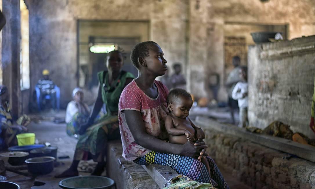 Mulher e filho de uma tribo de uma floresta do Congo buscam abrigo em uma fábrica abandonada na cidade de Nyunzu, após serem expulsos de sua região por conflitos armados: Brasil é um dos destinos buscados por refugiados Foto: SAMUEL ARANDA / NYT 22-3-16