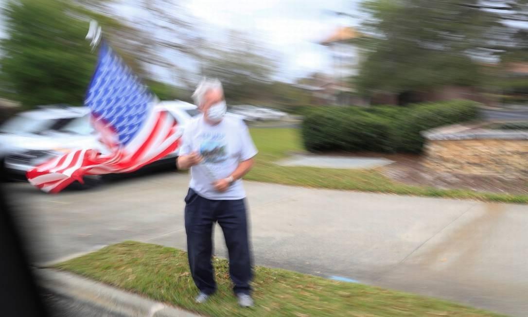 Um homem balançando uma bandeira dos Estados Unidos no estado da Flórida Foto: TOM BRENNER / REUTERS