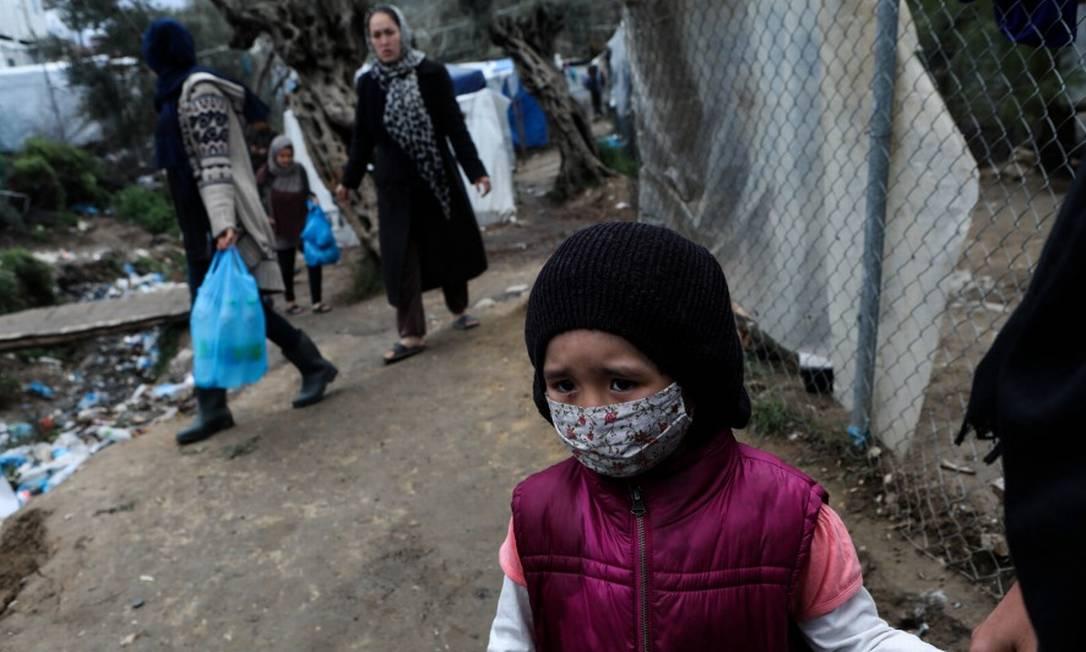 Menina com máscara de proteção em campo para refugiados e migrantes na ilha de Lesbos, na Grécia Foto: ELIAS MARCOU / REUTERS