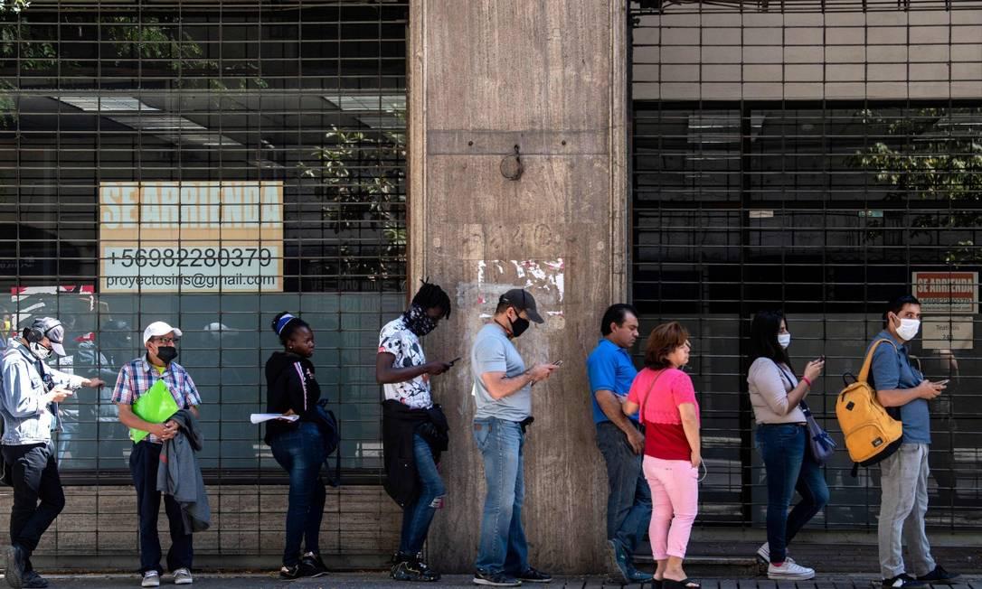 Pessoas usam máscara em fila para o recebe o auxílio-desemprego em Santiago Foto: MARTIN BERNETTI / AFP