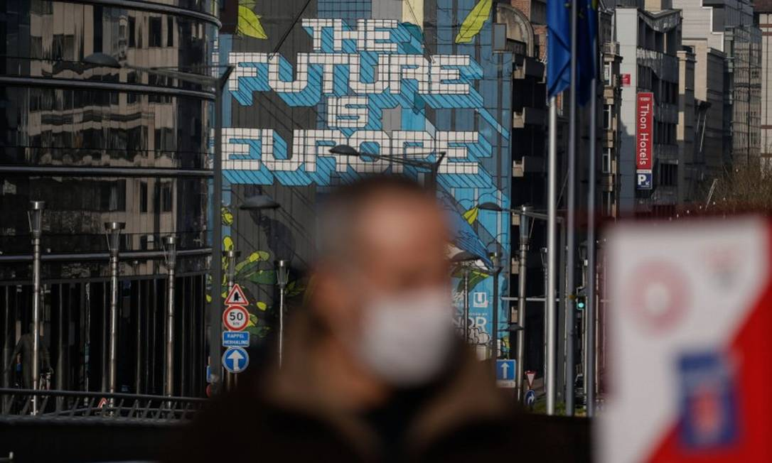 Um homem vestindo uma máscara caminha em frente à sede da Comissão Europeia em Bruxelas Foto: ARIS OIKONOMOU / AFP