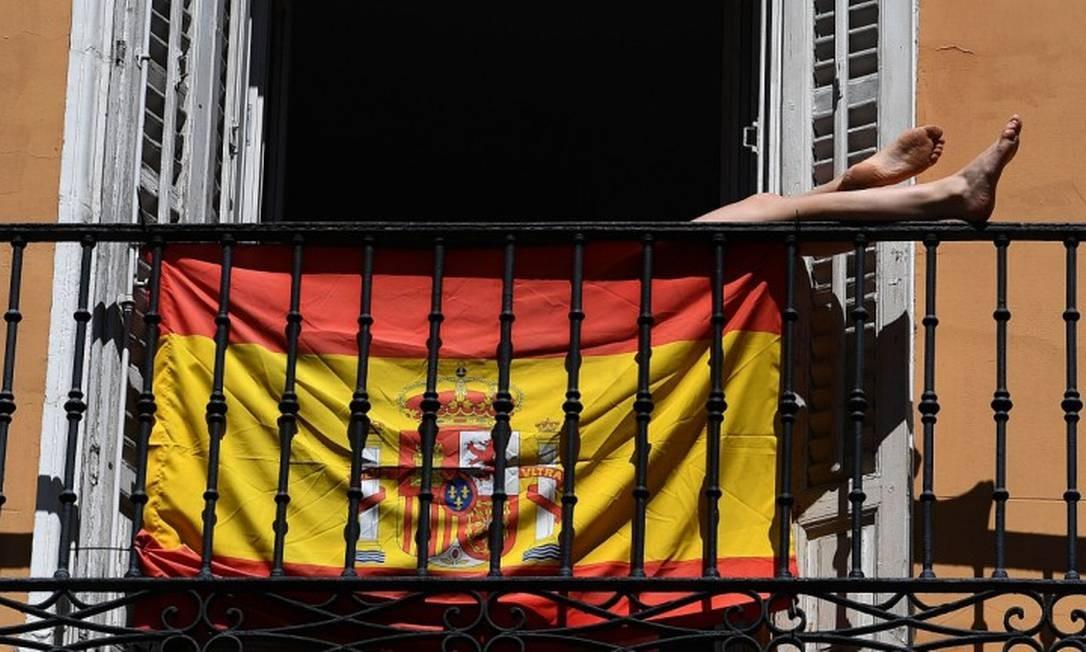 Mulher pega sol escondida atrás de uma bandeira da Espanha em sua varanda em Madri Foto: GABRIEL BOUYS / AFP