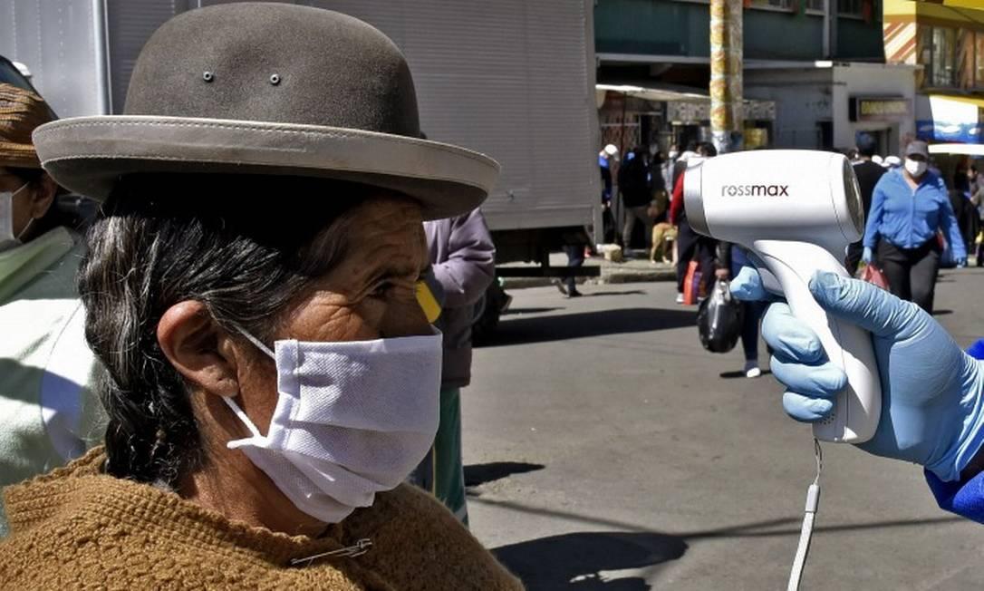 Uma mulher idosa tem a própria temperatura verificada por uma funcionária municipal de saúde em La Paz Foto: AIZAR RALDES / AFP