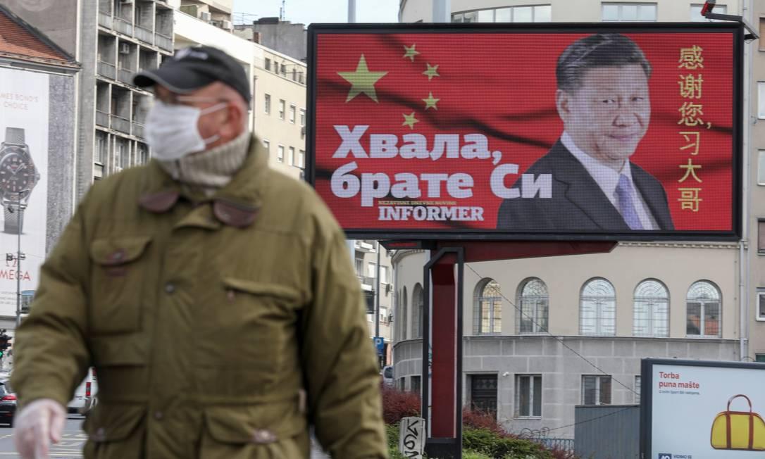 Homem de máscara em frente a outdoor com o presidente chinês Xi Jinping em Belgrado Foto: DJORDJE KOJADINOVIC / REUTERS