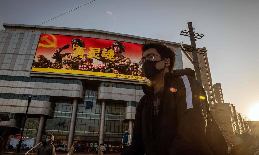 Jovem usando máscara em frente a sinal de trânsito em Pequim Foto: NICOLAS ASFOURI / AFP