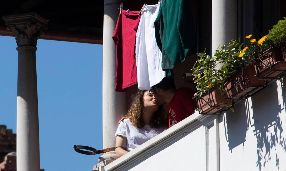 """Moradores do bairro de Garbatella em Roma se beijam no momento em que italianos foram para as janelas e balcões cantar """"Bella Ciao"""", hino da Resistência Foto: TIZIANA FABI / AFP"""