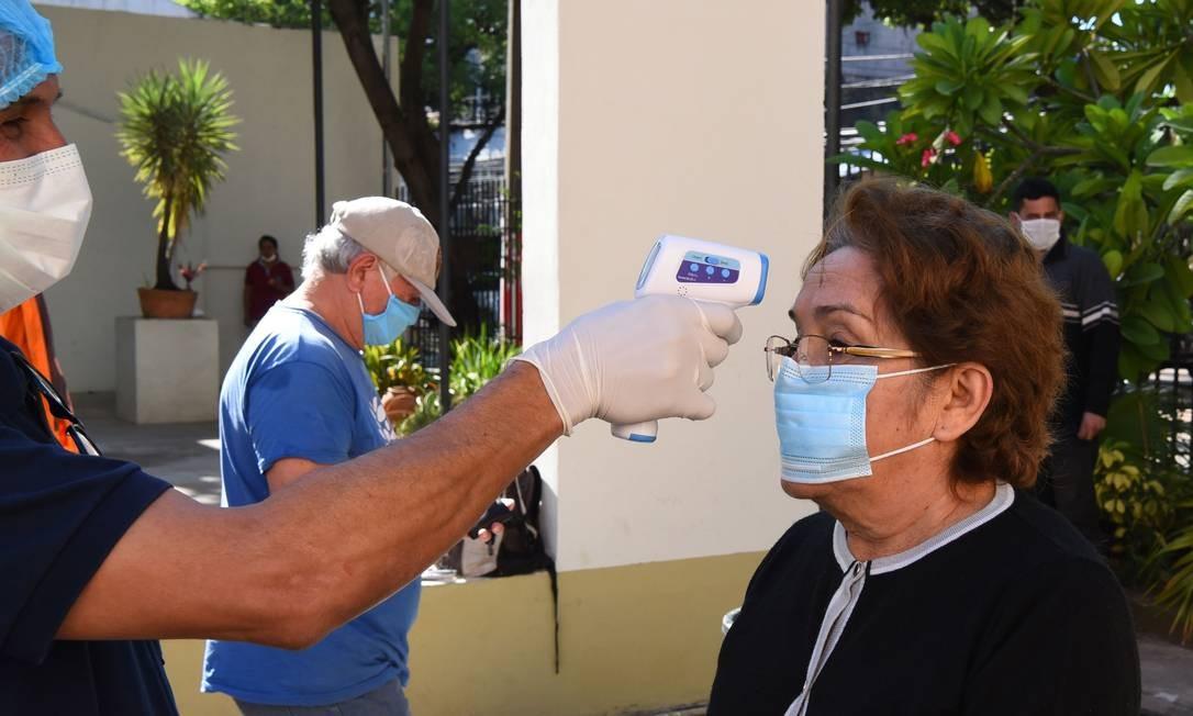 Profissional de saúde mede temperatura de idosa em Assunção, no Paraguai: país é um dos menos afetados na América Latina Foto: NORBERTO DUARTE / AFP