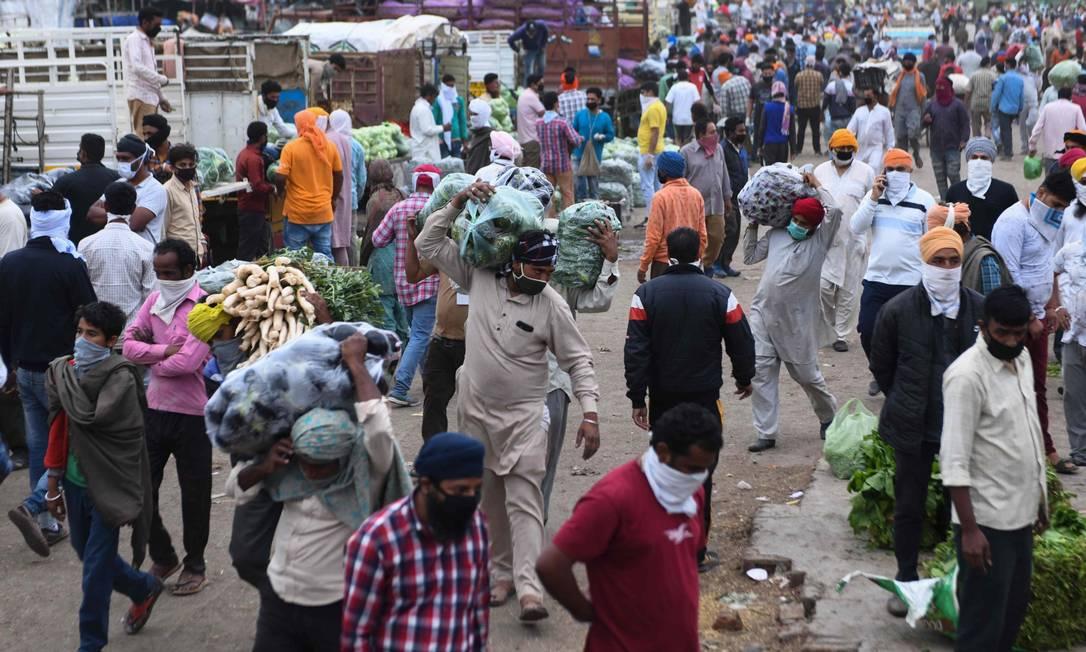 Indianos passam por uma rua: países emergentes enfrentam tripla ameaça, a própria pandemia, queda no comércio e fuga de capitais, disse Tooze Foto: NARINDER NANU / AFP