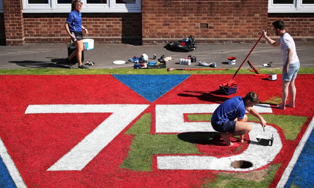 Equipe da Escola Primária Barnton, no Reino Unido, pintam o gramado em celebração ao aniversário de 75 anos na Segunda Guerra Mundial Foto: MOLLY DARLINGTON / REUTERS