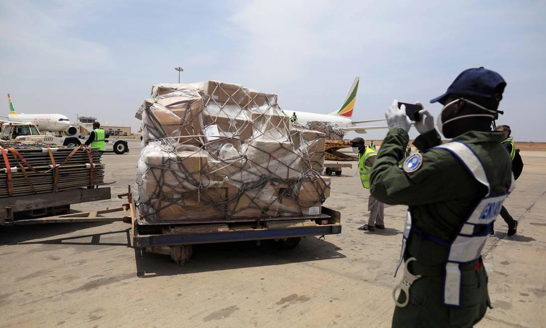 Um policial fotografa uma remessa de suprimentos médicos enviados pela Fundação Jack Ma em 28 de março no aeroporto Thies, no Senegal. Foto: ZOHRA BENSEMRA / REUTERS