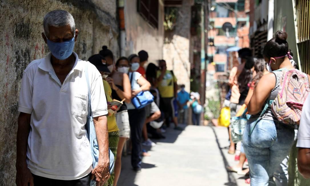 Pessoas fazem filas para receber comida em favela de Caracas Foto: MANAURE QUINTERO / REUTERS