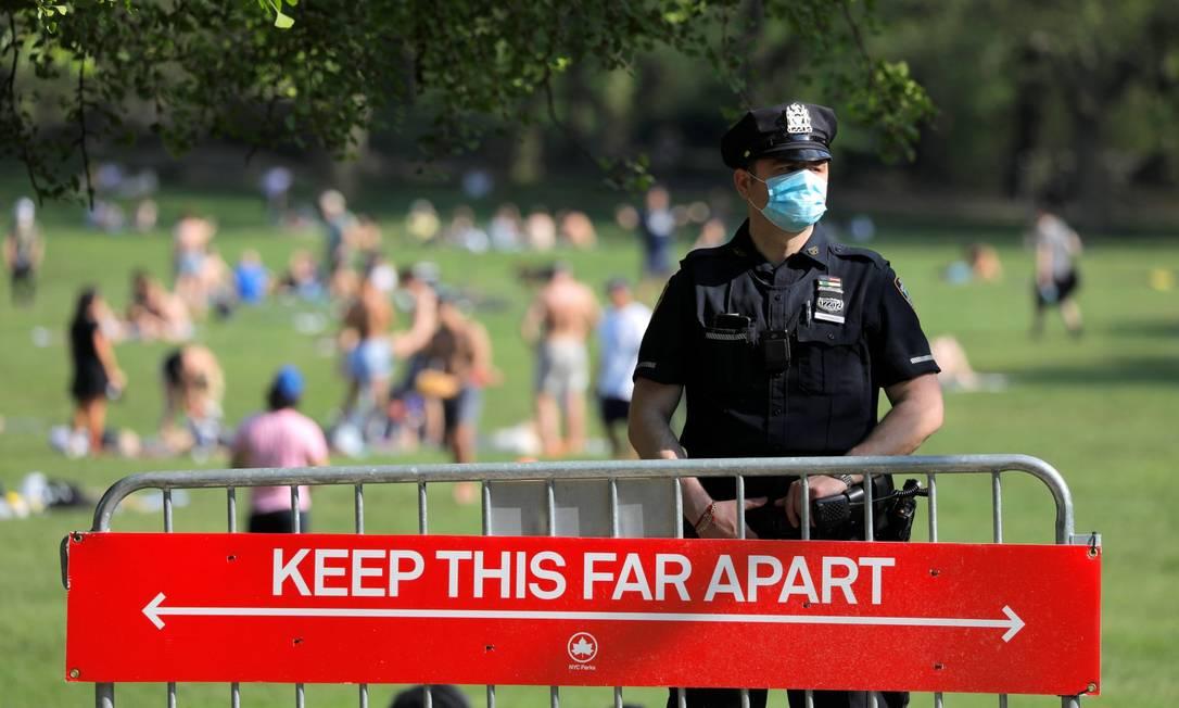 Policial em uma entrada do Central Park em Nova York, atrás de aviso para distância: com a chegada da primavera, parques têm enchido Foto: ANDREW KELLY / REUTERS