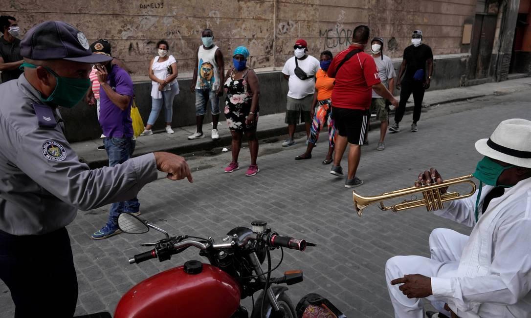 Policial chama a atenção do trompetista Carlos Sanchez a parar de tocar na frente das pessoas que, em fila, esperam para comprar comida: preocupação com a propagação do coronavírus Foto: ALEXANDRE MENEGHINI / REUTERS