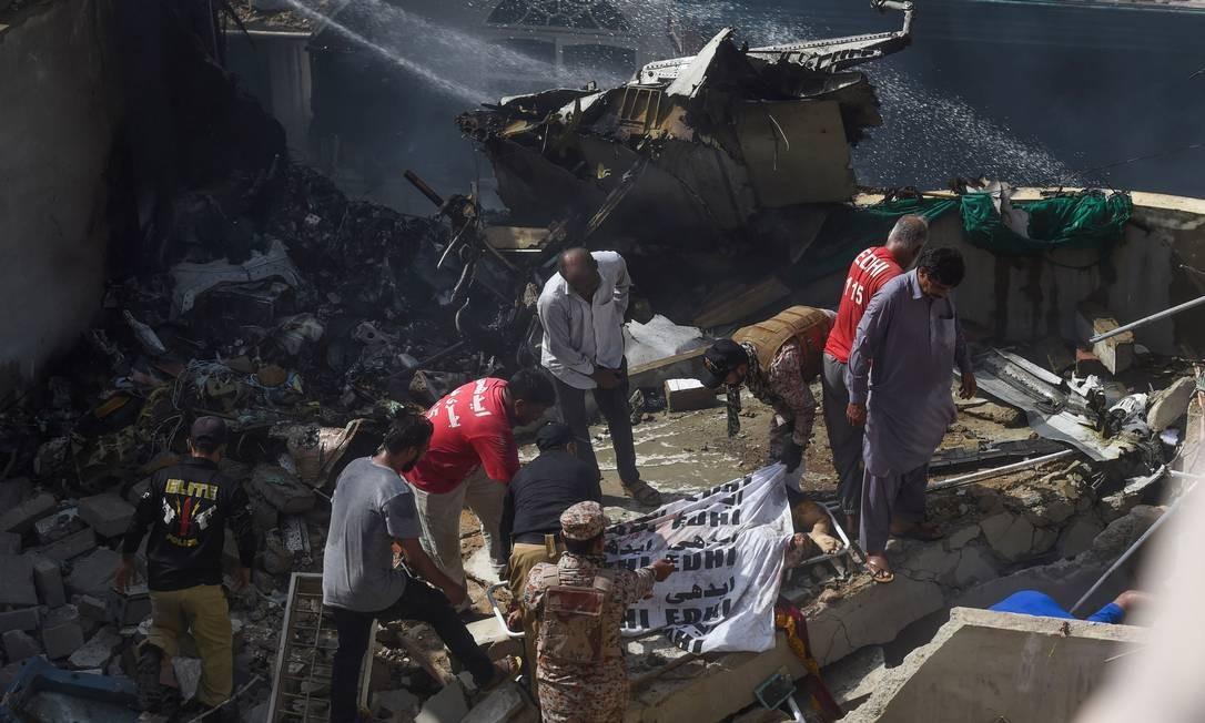 Equipes de resgate cobrem o corpo de uma vítima retirada dos escombros do avião da Pakistan International Airlines que caiu em um bairro residencial em Karachi, a 4 km do aeroporto, matando mais de 100 pessoas no Paquistão Foto: ASIF HASSAN / AFP