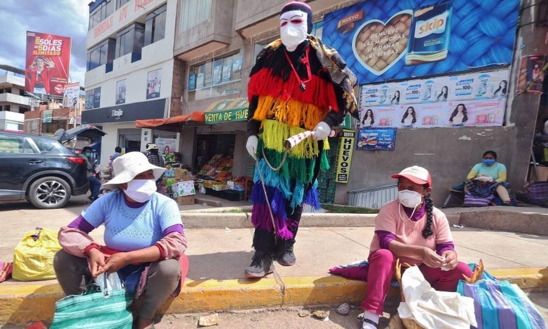 """Homem vestido em roupa tradicional """"ukukus"""" com um chicote na mão para intimidar as pessoas a irem para a casa em Cuzco Foto: JOSE CARLOS ANGULO / AFP"""
