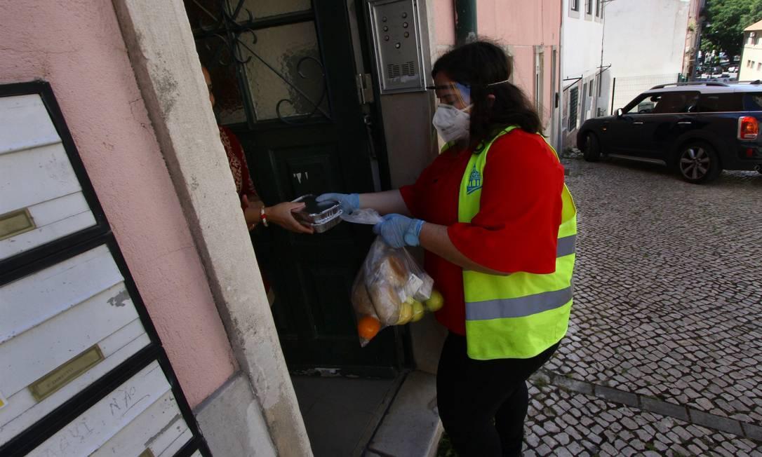 Funcionária distribui alimentos e refeições em Lisboa durante epidemia do novo coronavírus: programas apoiam pessoas que perderam o emprego Foto: Jorge Mantilla / Agência O Globo