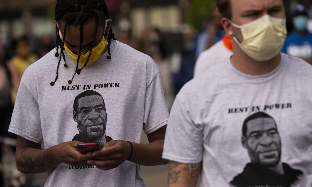 Dois homens usam camiseta com dizeres em homenagem a George Floyd: quatro policiais de Minneapolis foram demitidos depois que um vídeo feito por um espectador foi postado nas redes sociais mostrando Floy sendo sufocado por um policial Foto: Stephen Maturen / AFP