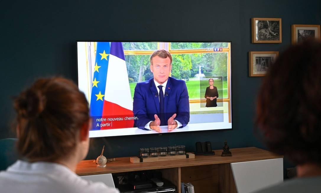 Família francesa assiste a discurso do presidente Emmanuel Macron pela televisão Foto: DENIS CHARLET / AFP