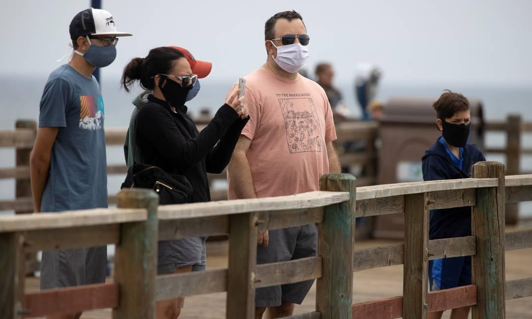 Pessoas usam máscaras enquanto caminham em píer, em Oceanside, na Califórnia: estado americano foi um dos que registraram ameaças a agentes da saúde pública. Foto: MIKE BLAKE / REUTERS
