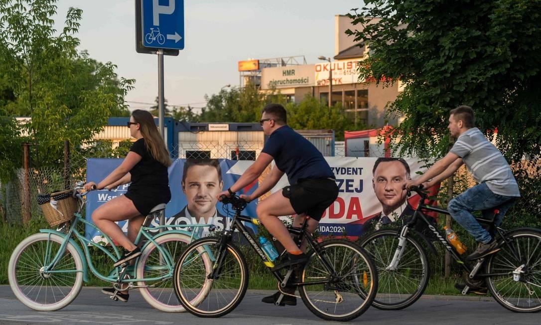 Ciclistas passam em frente a cartazes do opositor Rafal Trzaskowski e do atual presidente Andrzej Duda em um subúrbio de Varsóvia Foto: WOJTEK RADWANSKI / AFP
