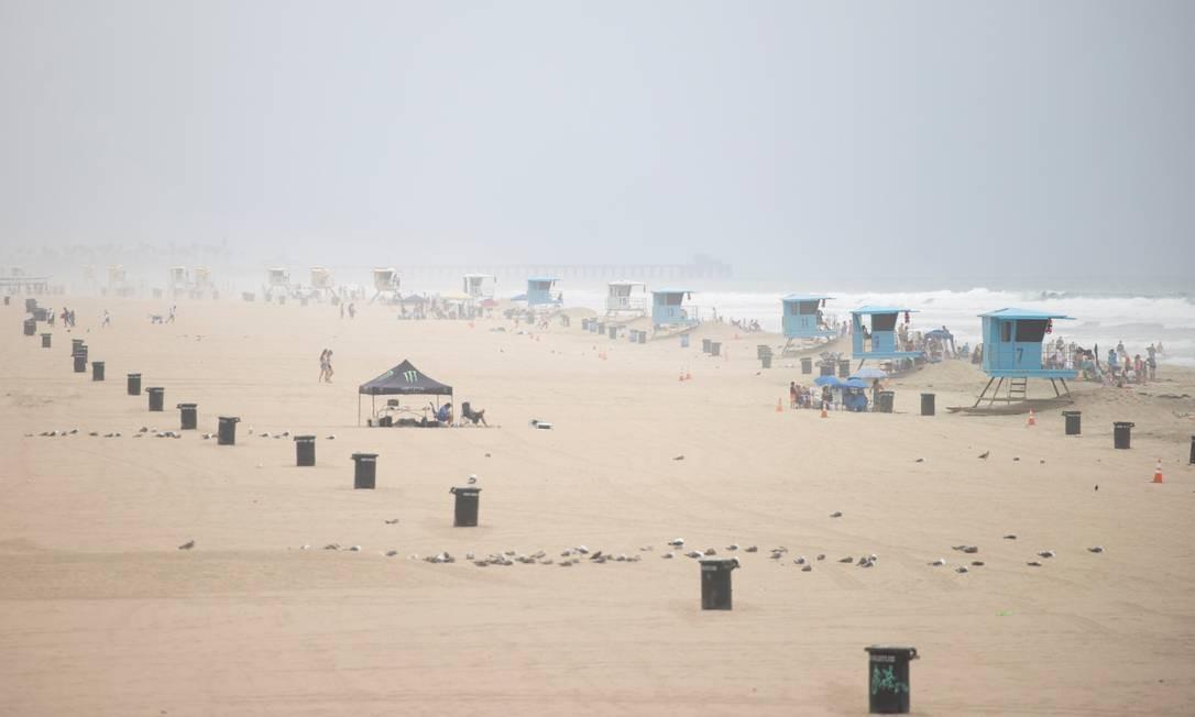 Pessoas se reúnem na manhã desta quarta-feira, início de julho, em Huntington Beach, em Orange, na Califórnia: ao menos as praias de Los Angeles, na Califórnia, vão fechar de novo Foto: MIKE BLAKE / REUTERS