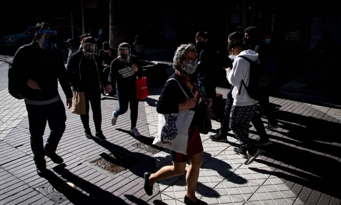 Pessoas usando máscras caminham na Plaza de Armas em Santiago Foto: MARTIN BERNETTI / AFP 15-7-20