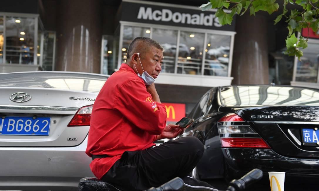 Motorista de aplicativo aguarda em frente a uma loja do McDonald's em Pequim Foto: GREG BAKER / AFP
