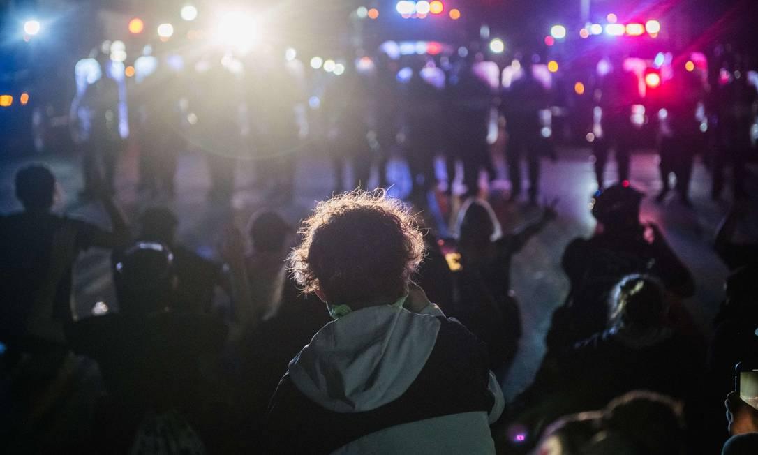 Manifestantes sentam-se em frente à barreira de policiais em Kenosha, no Wisconsin Foto: Brandon Bell / AFP