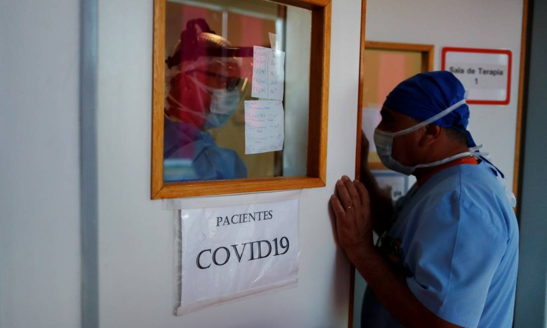 Os enfermeiros David Rosas e Alberto Loto falam na porta de uma UTI para tratar pacientes do coronavírus em Buenos Aires Foto: AGUSTIN MARCARIAN / REUTERS