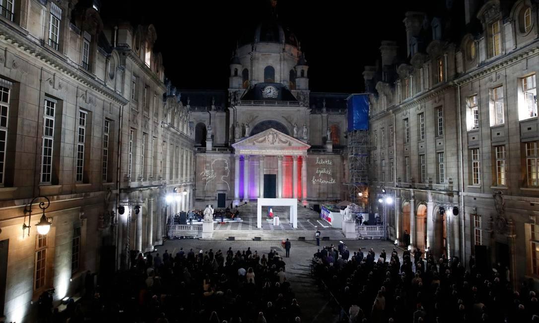 O presidente francês Emmanuel Macron, ao centro, faz uma homenagem ao professor Samuel Paty em frente ao caixão do mesmo na Sorbonne Foto: FRANCOIS MORI / AFP