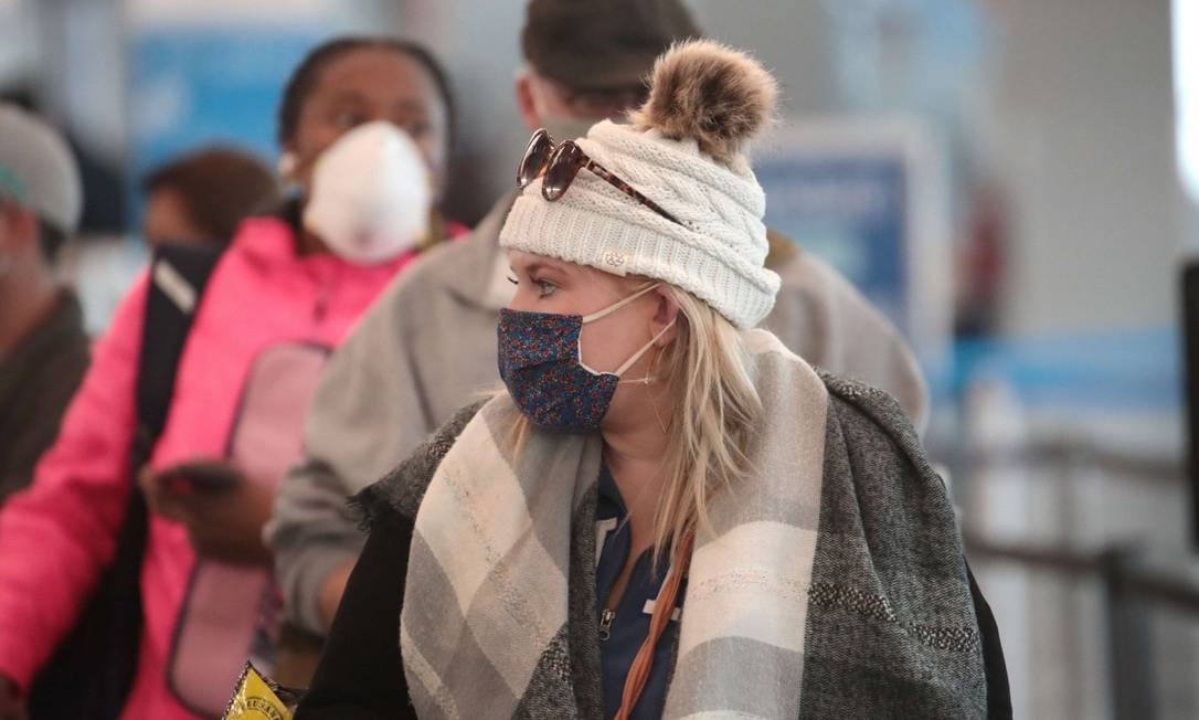 Mulher de máscara no aeroporto de Chicago, em Illinois: estado terá novas restrições a partir desta quarta-feira Foto: SCOTT OLSON / AFP