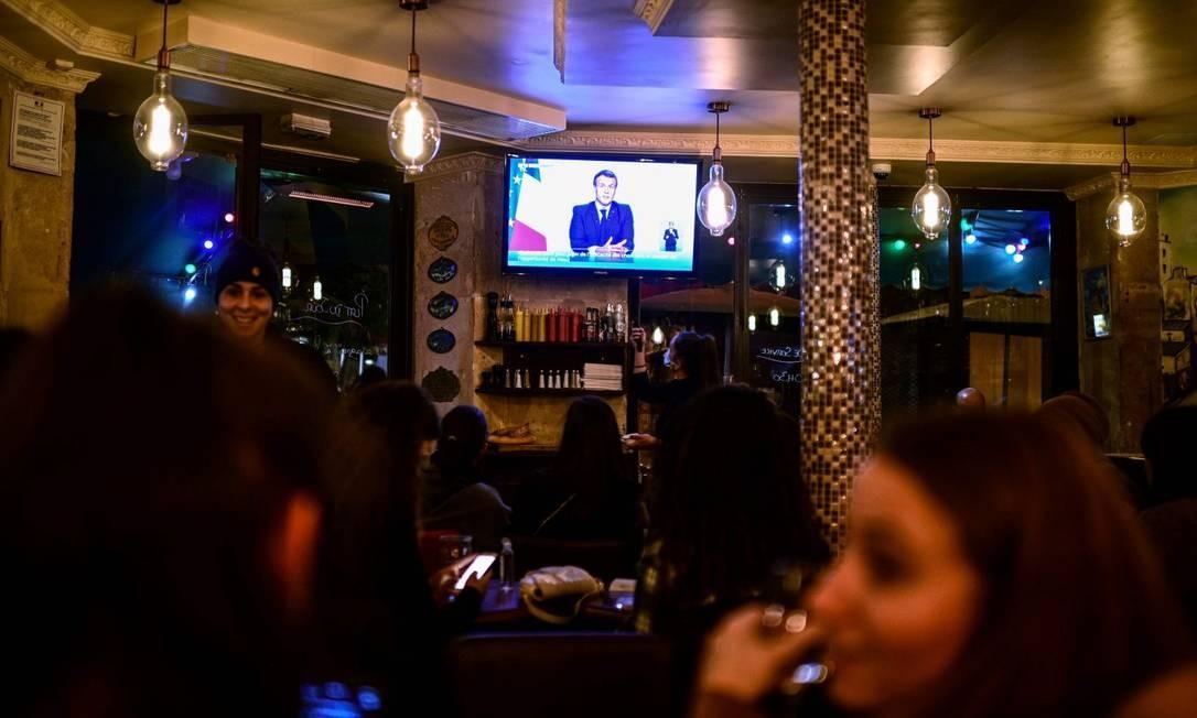 Pessoas em café em Paris assistem ao anúncio pela TV de uma nova quarentena no país Foto: MARTIN BUREAU / AFP