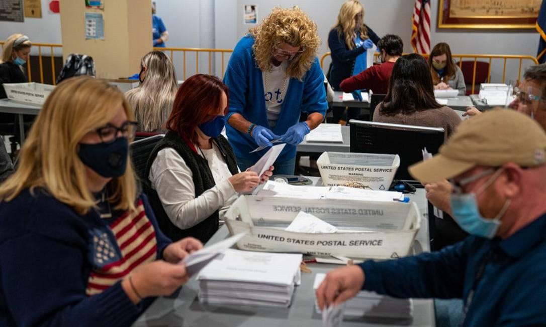 Funcionários eleitorais verificam envelopes em Scranton, Pensilvânia: A entrega de votos por carta devido à pandemia torna o processo de apuração mais demorado Foto: ROBERT NICKELSBERG / Agência O Globo