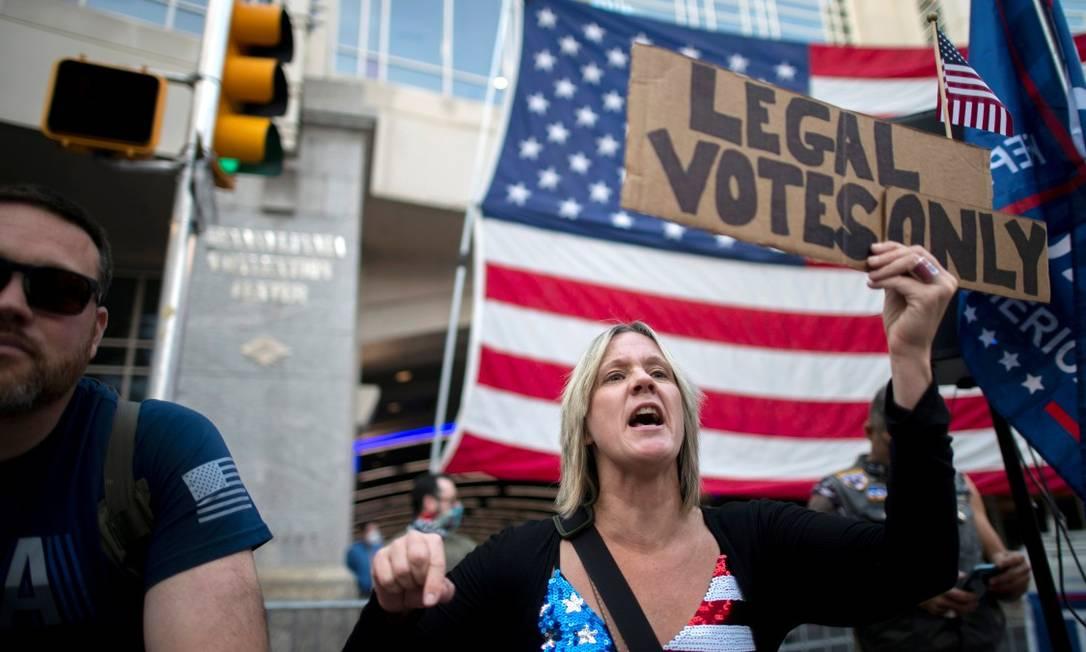 """Carri Dusza, uma apoiadora de Donald Trump, segura um cartaz onde se lê """"apenas votos legais"""", em frente a um centro de contagem na Pensilvânia, um dos estados com maior número de processos por parte do presidente Foto: MARK MAKELA / REUTERS"""