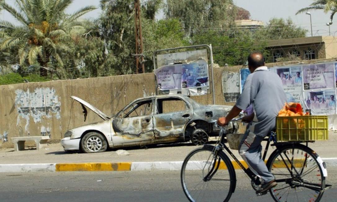 Em 20 de setembro de 2007, um iraquiano anda de bicicleta passando por restos de um carro, queimado depois que guardas da Blackwater abriram fogo e cometeram um massacre contra civis em Bagdá Foto: ALI YOUSSEF / AFP
